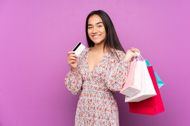Jonge indiase vrouw geïsoleerd op paarse muur met boodschappentassen en een creditcard