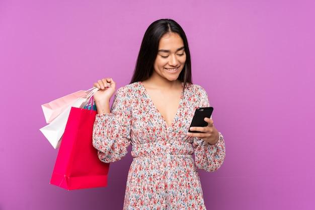 Jonge indiase vrouw geïsoleerd op paarse muur met boodschappentassen en het schrijven van een bericht met haar mobiele telefoon naar een vriend
