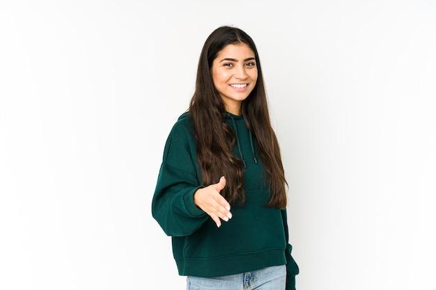 Jonge indiase vrouw geïsoleerd op paarse ruimte uitrekkende hand op camera in groetgebaar.