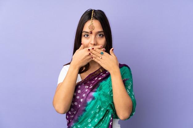Jonge indiase vrouw geïsoleerd op paarse wandbekleding mond met handen