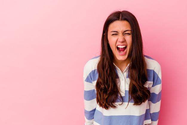Jonge indiase vrouw geïsoleerd op roze achtergrond schreeuwen erg boos, woede concept, gefrustreerd.