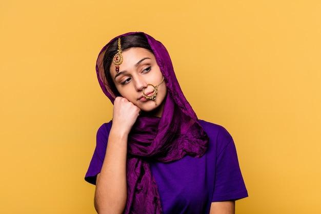 Jonge indiase vrouw, gekleed in een traditionele sari kleding geïsoleerd op geel die zich verdrietig en peinzend voelt, kijkend naar kopie ruimte.