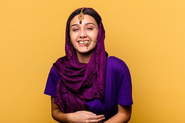 Jonge indiase vrouw, gekleed in een traditionele sari kleding op geel lachen en plezier hebben.
