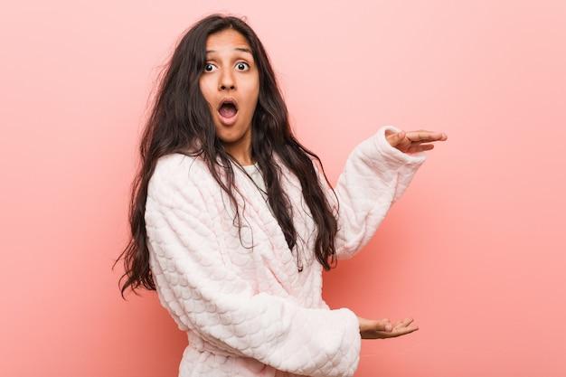 Jonge indiase vrouw, gekleed in pyjama geschokt en verbaasd met een kopie ruimte tussen handen.