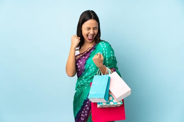 Jonge indiase vrouw met boodschappentassen een overwinning vieren