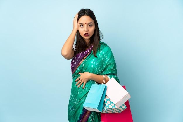 Jonge indiase vrouw met boodschappentassen met een uitdrukking van frustratie en niet begrijpen