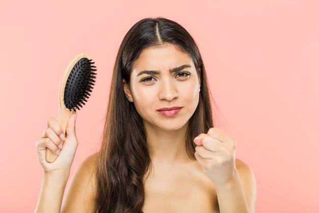 Jonge indiase vrouw met een haarborstel met vuist, agressieve gezichtsuitdrukking.