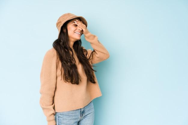 Jonge indiase vrouw met een hoed lacht vreugdevol handen op het hoofd te houden. geluk concept.