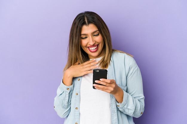 Jonge indiase vrouw met een telefoon geïsoleerd lacht hardop hand op de borst te houden.