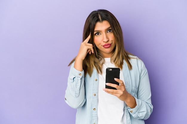 Jonge indiase vrouw met een telefoon geïsoleerd wijzende tempel met vinger, denken, gericht op een taak.