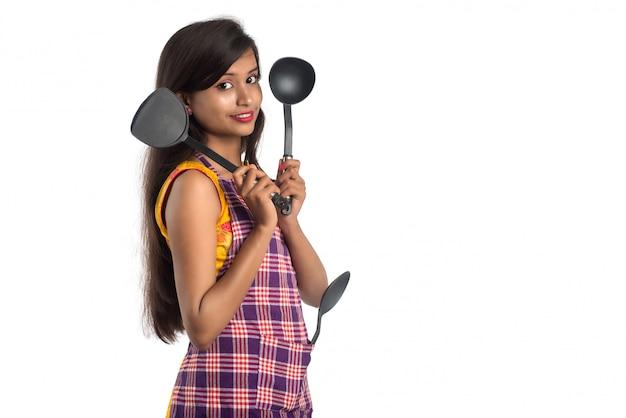 Jonge indiase vrouw met keukengerei (lepel, nietje, pollepel, pan, enz.) op een wit