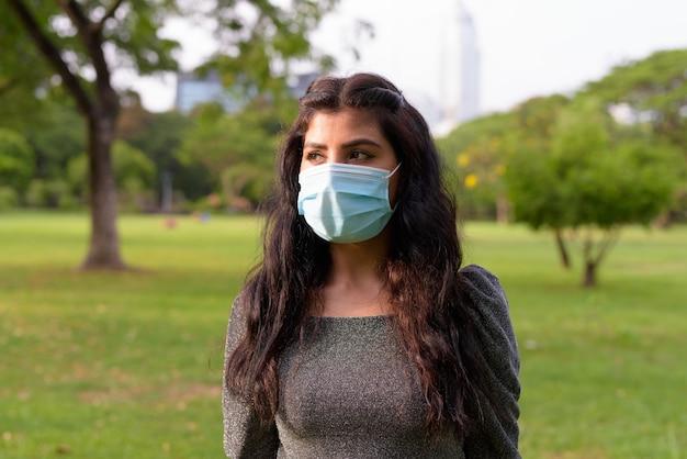 Jonge indiase vrouw met masker denken terwijl u ontspant in het park