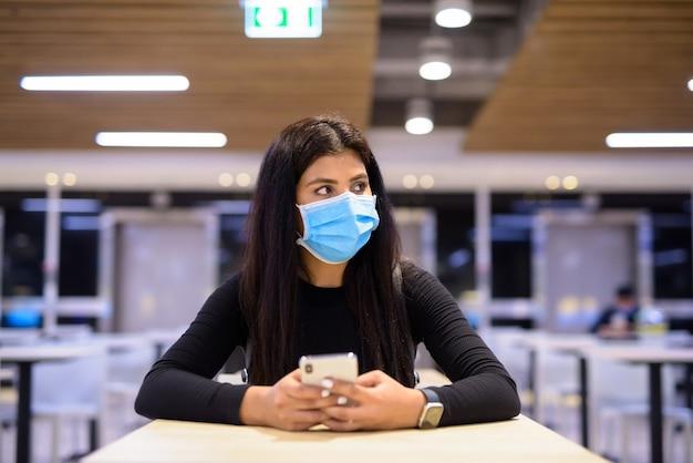 Jonge indiase vrouw met masker denken tijdens het gebruik van telefoon en zitten met afstand op food court