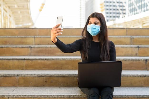Jonge indiase vrouw met masker met behulp van laptop en videobellen met telefoon door de trap in de stad