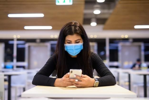 Jonge indiase vrouw met masker met behulp van telefoon en zittend met afstand op food court
