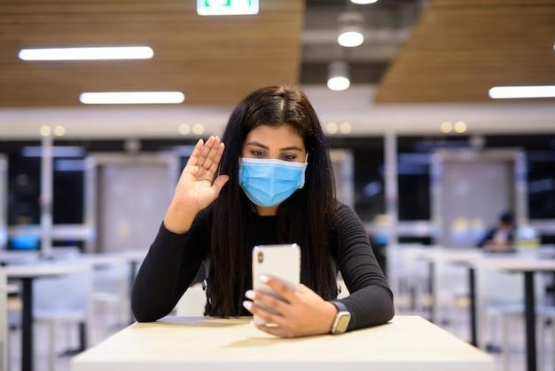 Jonge indiase vrouw met masker videobellen met behulp van telefoon en zittend met afstand op food court
