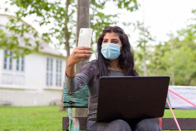 Jonge indiase vrouw met masker videobellen met behulp van telefoon zittend met afstand op een bankje