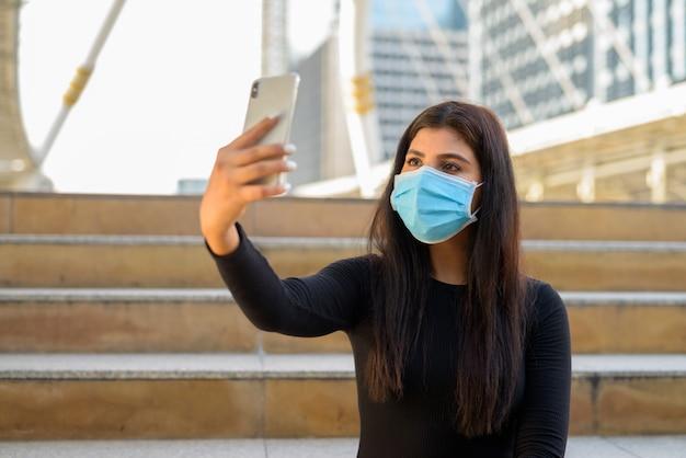 Jonge indiase vrouw met masker videobellen met telefoon en zittend bij de trap in de stad