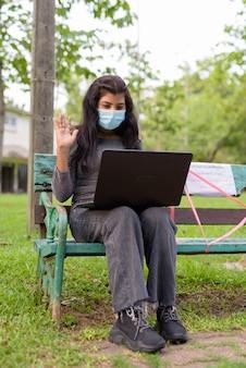 Jonge indiase vrouw met masker videobellen zittend met afstand op bankje