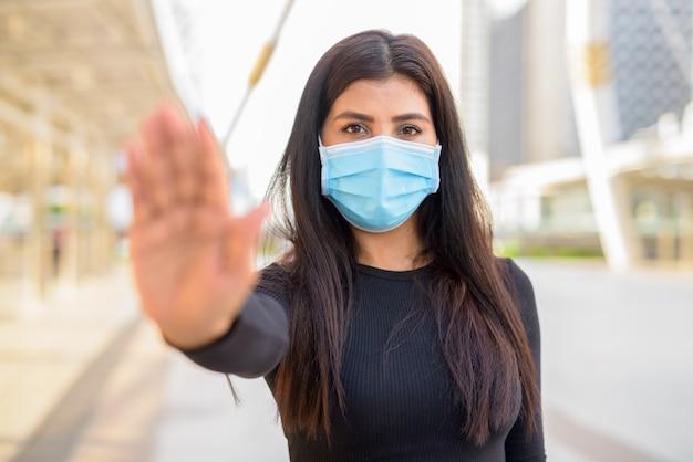 Jonge indiase vrouw met masker voor bescherming tegen uitbraak van het coronavirus met stopgebaar in de stad
