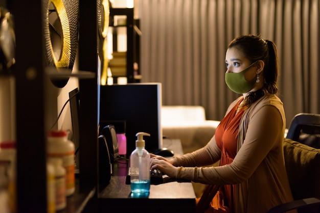Jonge indiase vrouw met masker werken 's avonds laat vanuit huis tijdens quarantaine