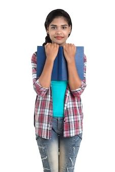 Jonge indiase vrouw met rugzak staande te houden notebooks, poseren op een witte muur.