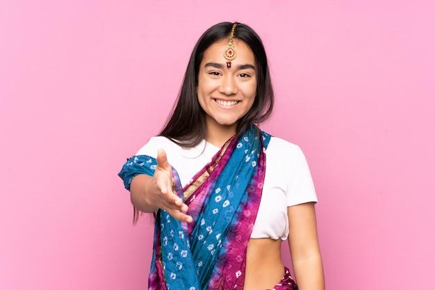 Jonge indiase vrouw met sari over muur handen schudden voor het sluiten van een goede deal