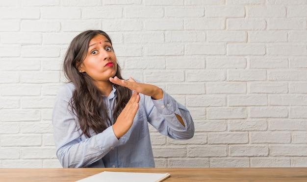 Jonge indiase vrouw moe en verveeld, het maken van een time-out gebaar, moet stoppen vanwege werkstress