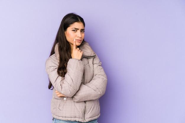 Jonge indiase vrouw ongelukkig kijken met sarcastische uitdrukking.