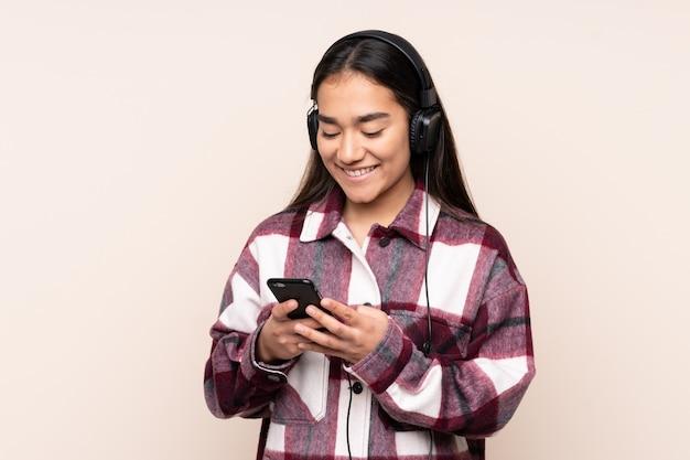 Jonge indiase vrouw op beige muur luisteren muziek en op zoek naar mobiel