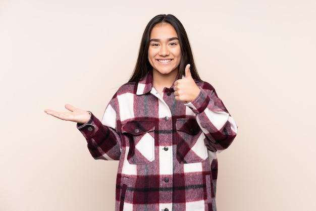 Jonge indiase vrouw op beige muur met lege ruimte op de palm en met duimen omhoog