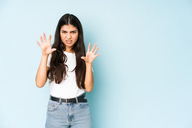 Jonge indiase vrouw op blauw met klauwen die een kat, agressief gebaar imiteren.