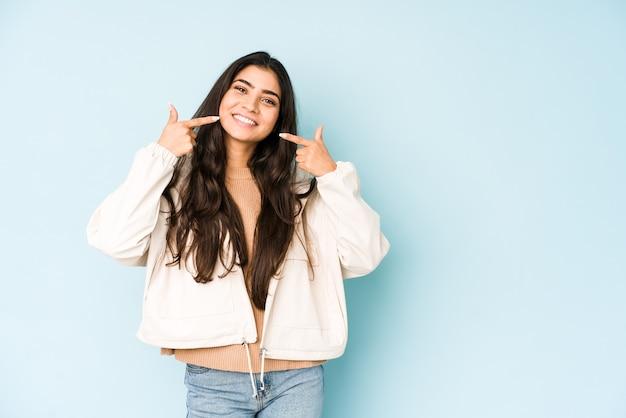 Jonge indiase vrouw op blauwe ruimte glimlacht, wijzende vingers naar mond.