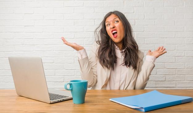 Jonge indiase vrouw op kantoor gek en wanhopig, schreeuwen uit de hand, grappige gek uiten vrijheid en wilde