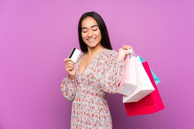 Jonge indiase vrouw op paarse muur met boodschappentassen en een creditcard