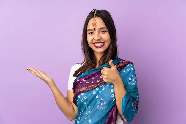 Jonge indiase vrouw op paarse muur met lege ruimte op de palm en met duimen omhoog