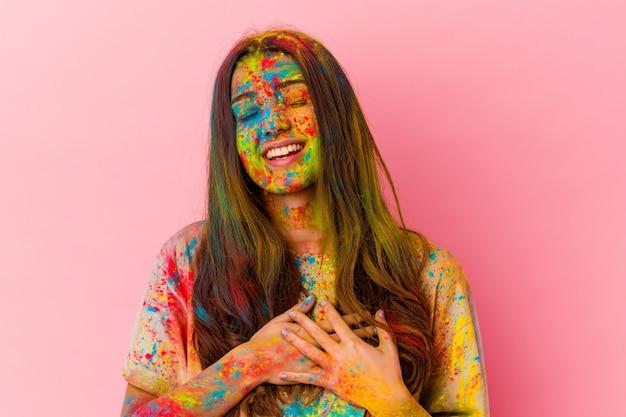 Jonge indiase vrouw vieren heilig festival geïsoleerd op wit lachen houden handen op hart, concept van geluk.