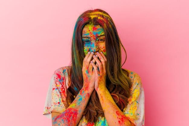 Jonge indiase vrouw vieren heilig festival geïsoleerd op wit lachen om iets, mond bedekken met handen.