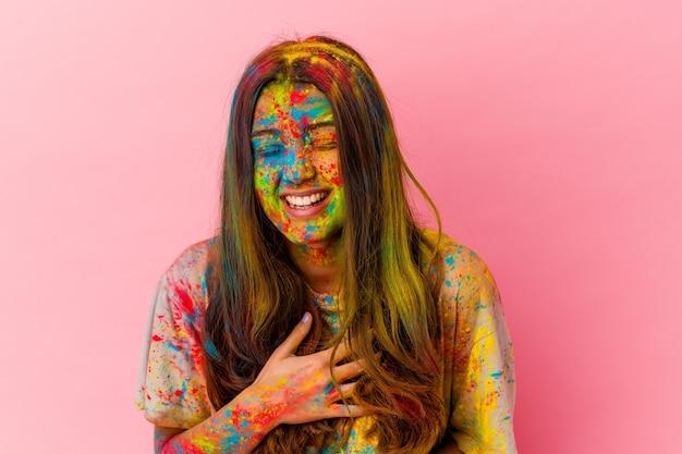Jonge indiase vrouw vieren heilig festival geïsoleerd op wit lacht vrolijk en heeft plezier met handen op de buik.