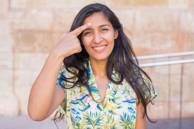Jonge indiase vrouw wijst met haar voorhoofd op straat