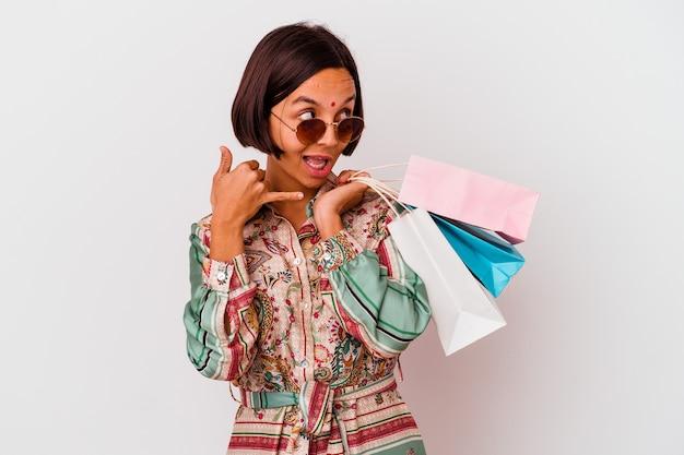 Jonge indiase vrouw winkelen wat kleren geïsoleerd op een witte achtergrond met een mobiele telefoongesprek gebaar met vingers.