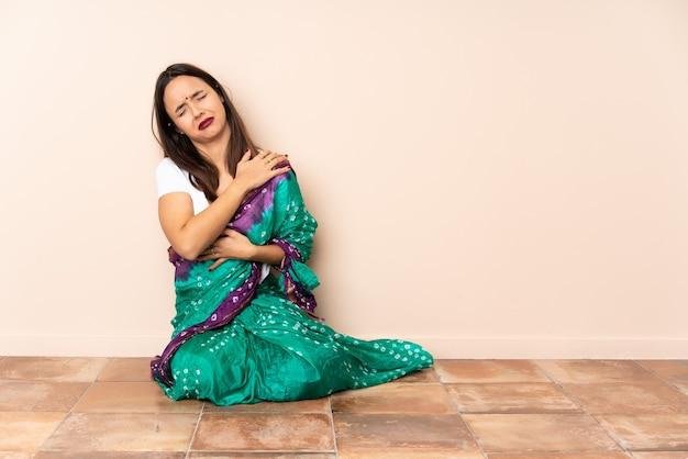 Jonge indiase vrouw zittend op de vloer die lijdt aan pijn in de schouder omdat ze zich heeft ingespannen