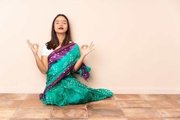 Jonge indiase vrouw zittend op de vloer in zen pose