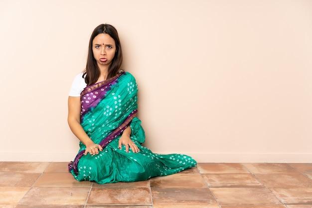 Jonge indiase vrouw zittend op de vloer met droevige uitdrukking