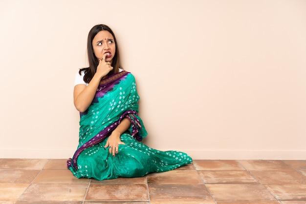 Jonge indiase vrouw zittend op de vloer nerveus en bang