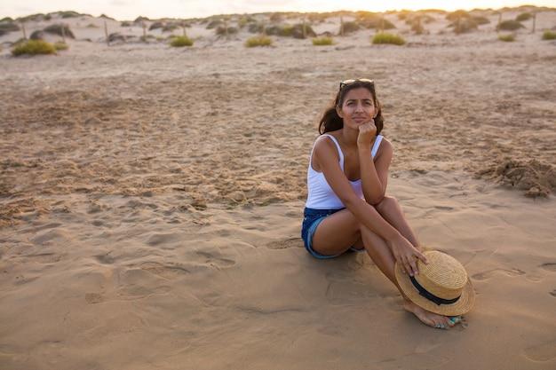 Jonge indiase vrouw zittend op het strand