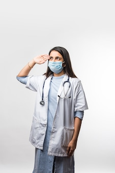 Jonge indiase vrouwelijke arts met medisch gezichtsmasker die salueert terwijl hij geïsoleerd tegen een witte muur staat