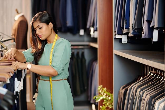 Jonge indiase winkelbediende met meetlint op zoek naar de beste broek voor klant in de winkel