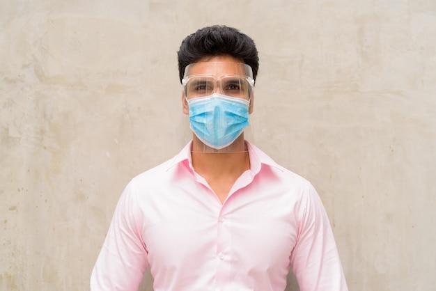 Jonge indiase zakenman die masker en gelaatsscherm draagt ter bescherming tegen uitbraak van het coronavirus buitenshuis