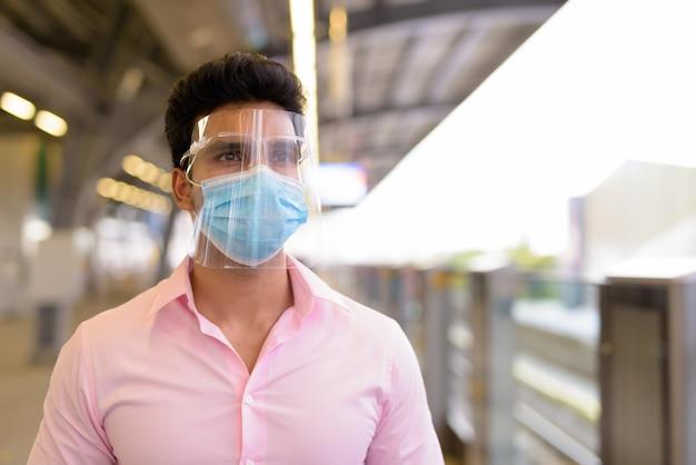 Jonge indiase zakenman die met masker en gezichtsschild bij het hemelstation wacht